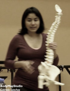 Gabriela holding a spine model
