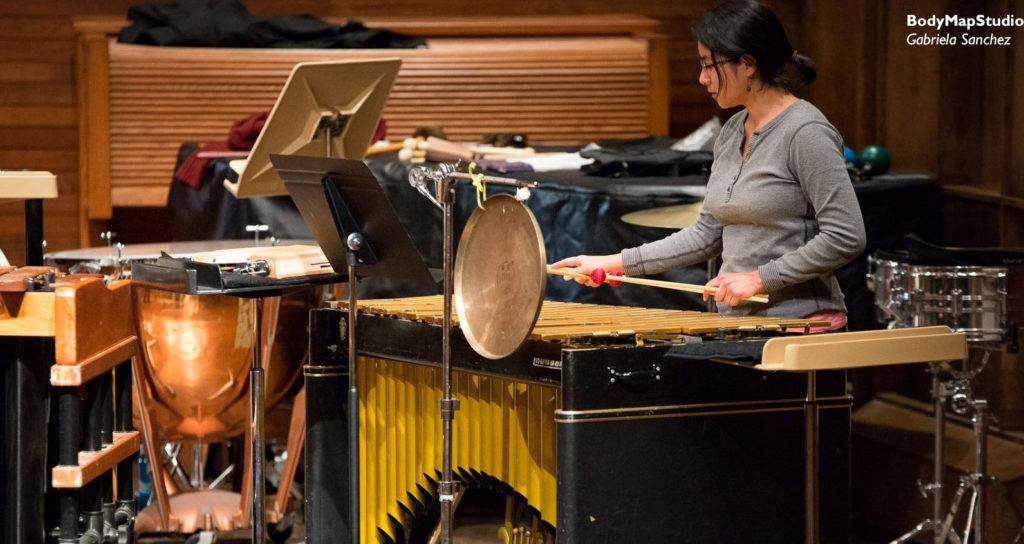 Una sala de conciertos con instrumentos de percusión y Gabriela Sanchez tocando el vibráfono.