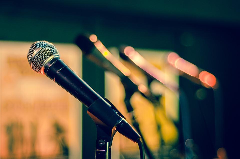 Micrófonos alineados en el escenario.